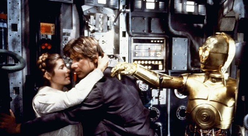 Carrie Fisher, Harrison Ford e Anthony Daniels no set de filmagens de Star Wars.